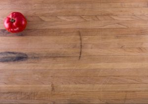 A background image of a cutting board featuring a ripe tomato