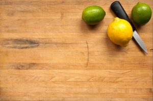 A background image of a cutting board with two limes and a lemon