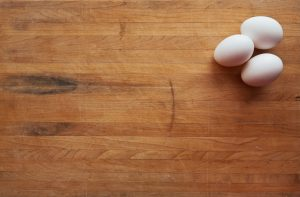 A background image of a cutting board with 3 eggs on it