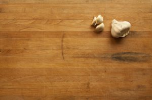 A background image of a cutting board with garlic cloves