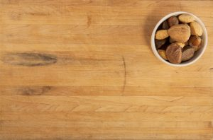 A background image of a cutting board and a bowl of various nuts