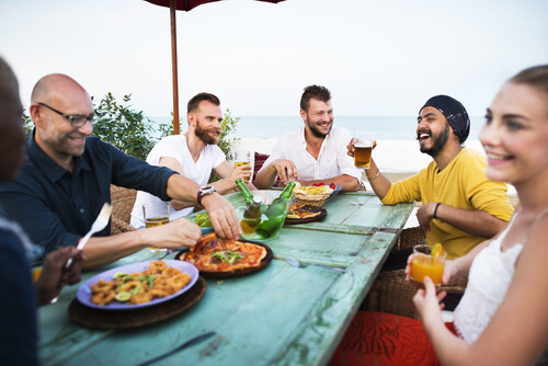 Young people enjoying food and drinks at a scenic beach bar